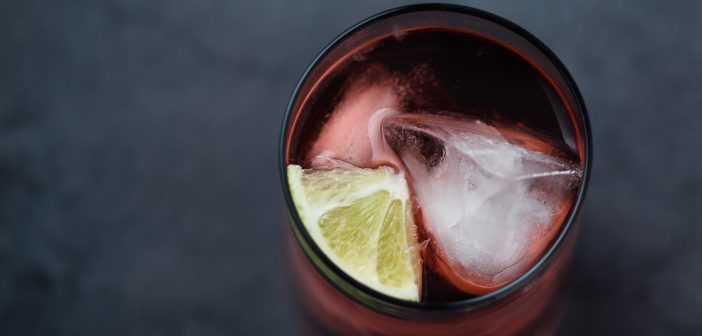 An above shot of a rum punch garnished with a lime wedge on a gray surface.