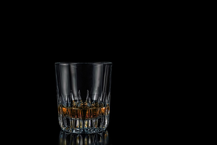 A glass of dark of bourbon